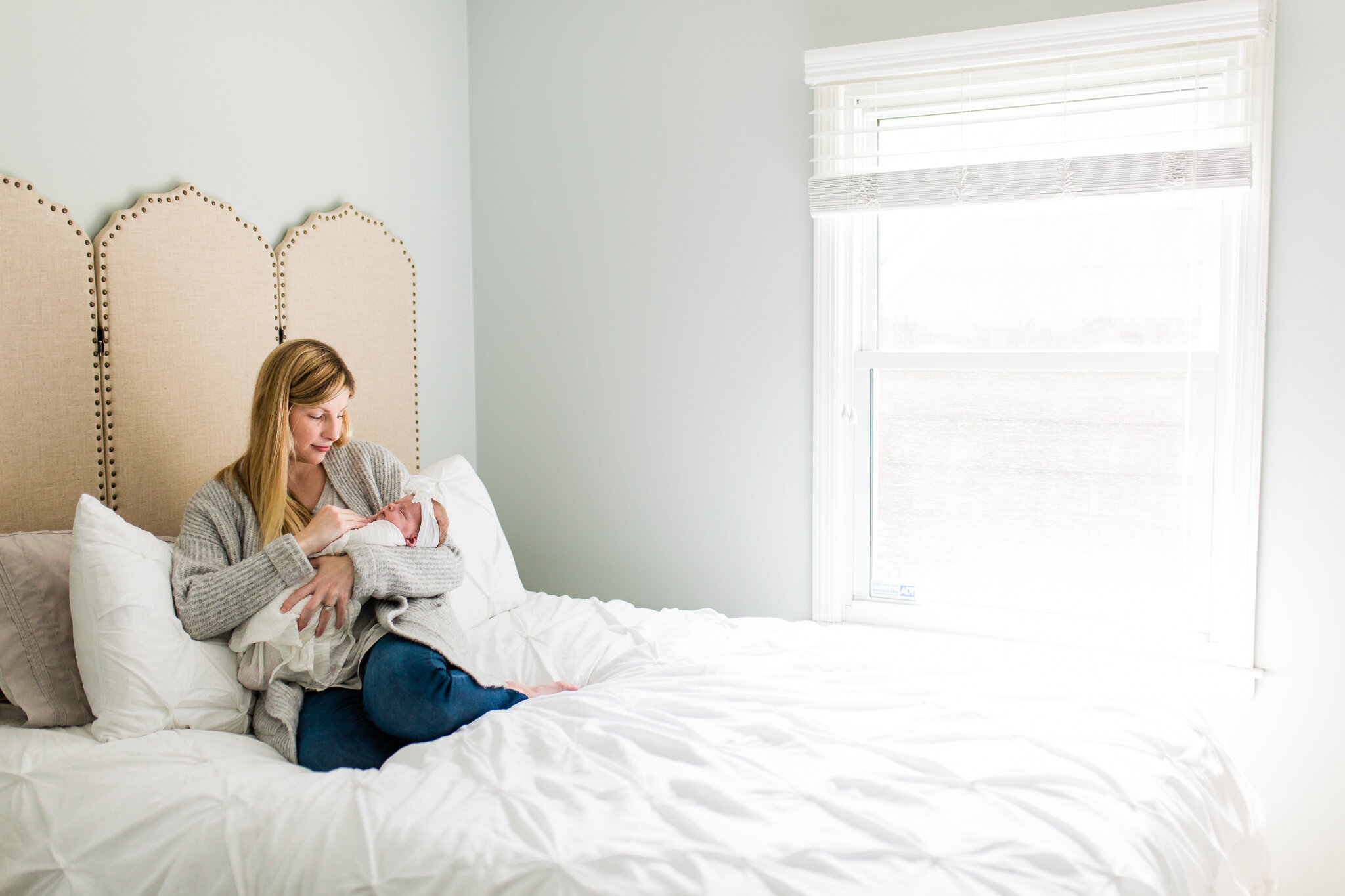 Mother cuddles her newborn daughter on the bed, Prarie Village Kansas light in home newborn session, Rebecca Clair Photography