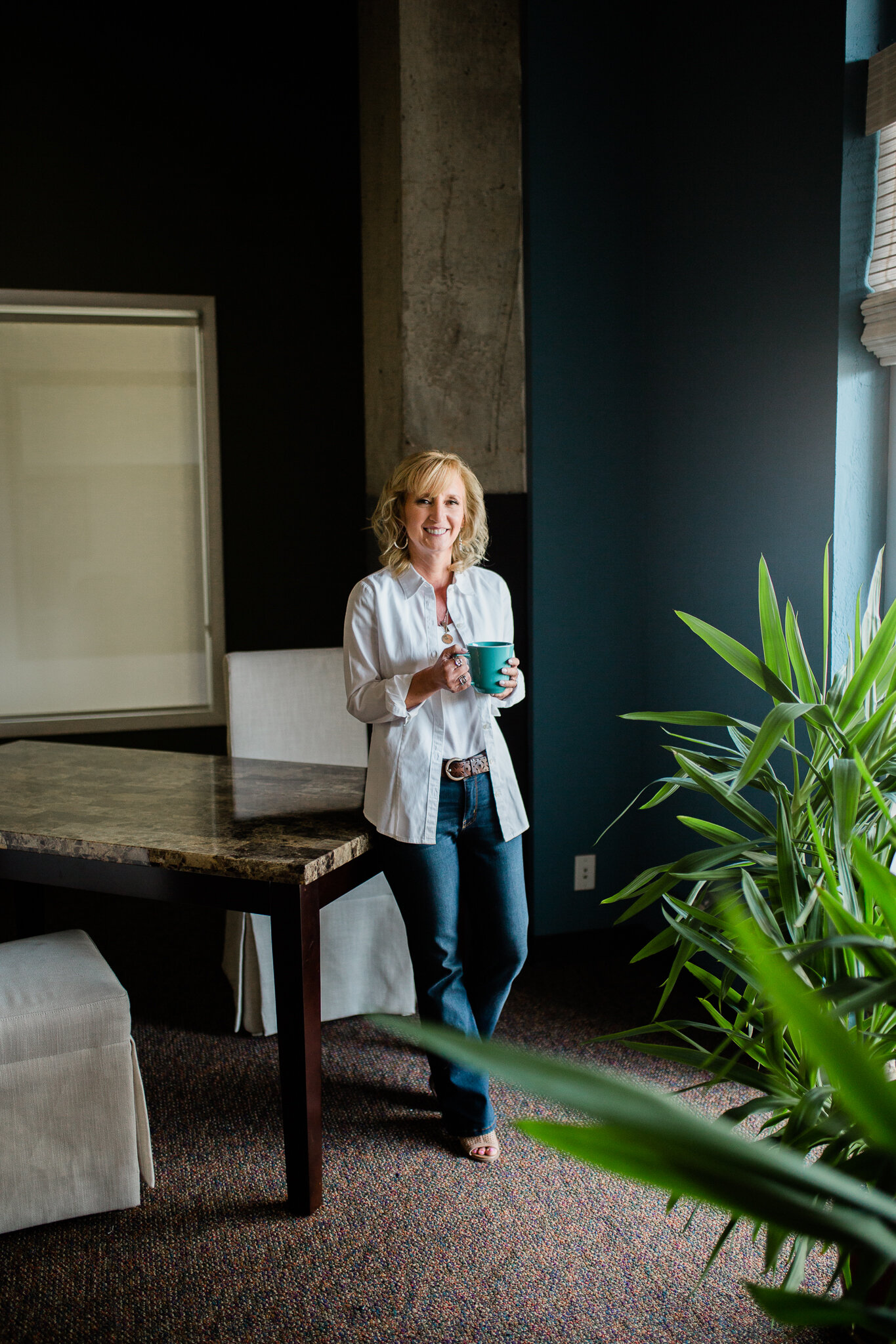 Business woman stands comfortably by a table with coffee, Kansas City casual headshot session, Rebecca Clair Photography