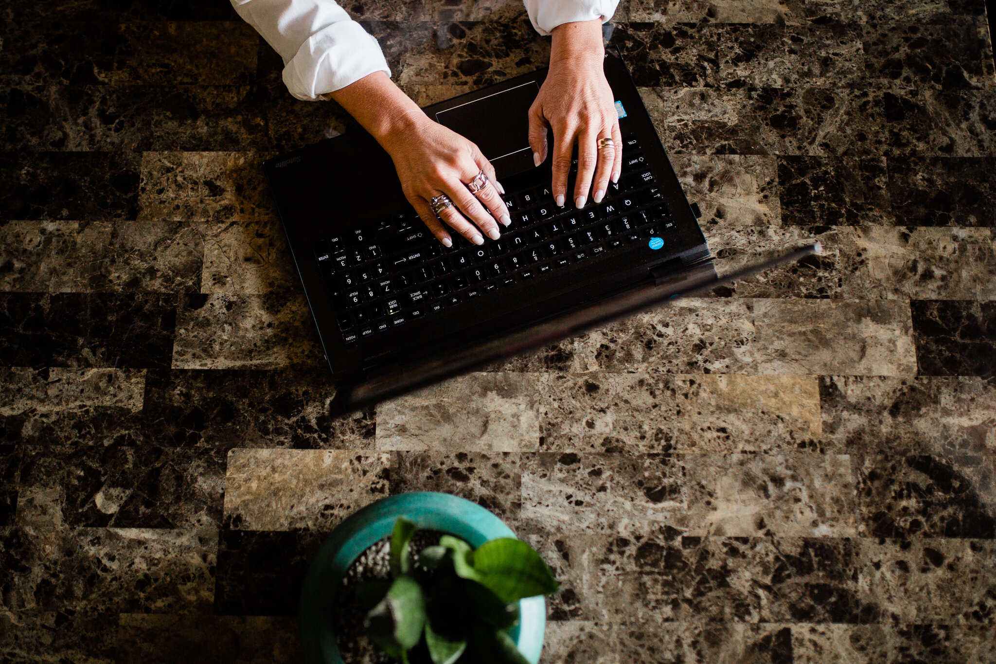 Arial photo of a woman typing on a laptop computer at a table with a plant, Kansas City creative branding photo session, Rebecca Clair Photography