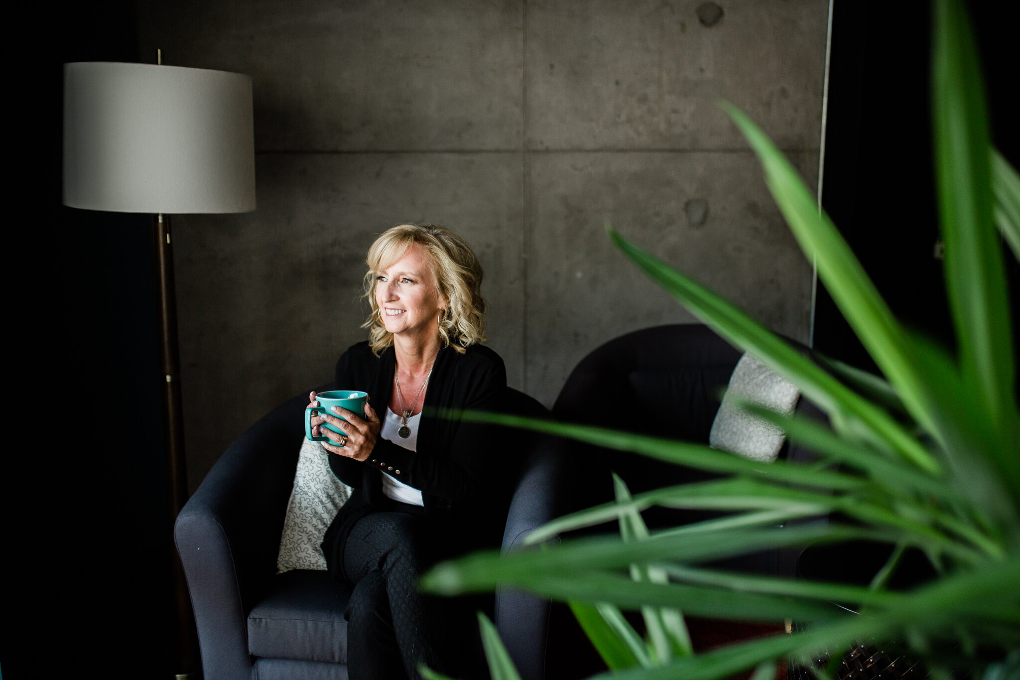 Woman sits in her office holding coffee, Kansas City branding session, Rebecca Clair Photography