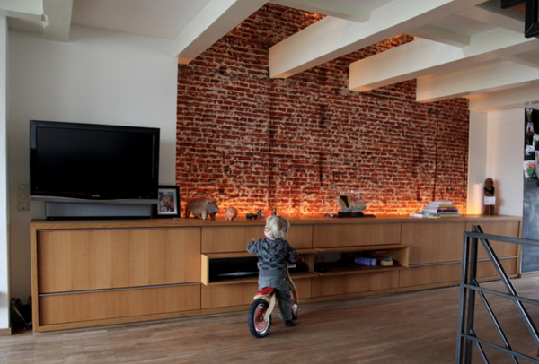 Brick wall illuminated from below by built in light fixtures placed behind furniture.