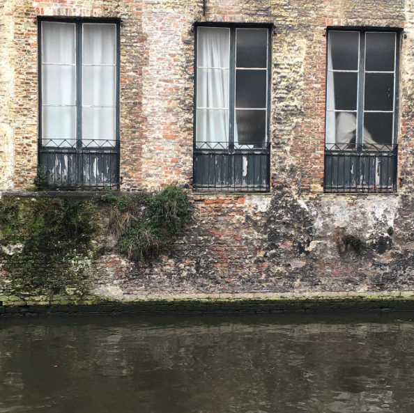 Bruges, Belgium. Brick wall of a building surrounded by water of the canal.