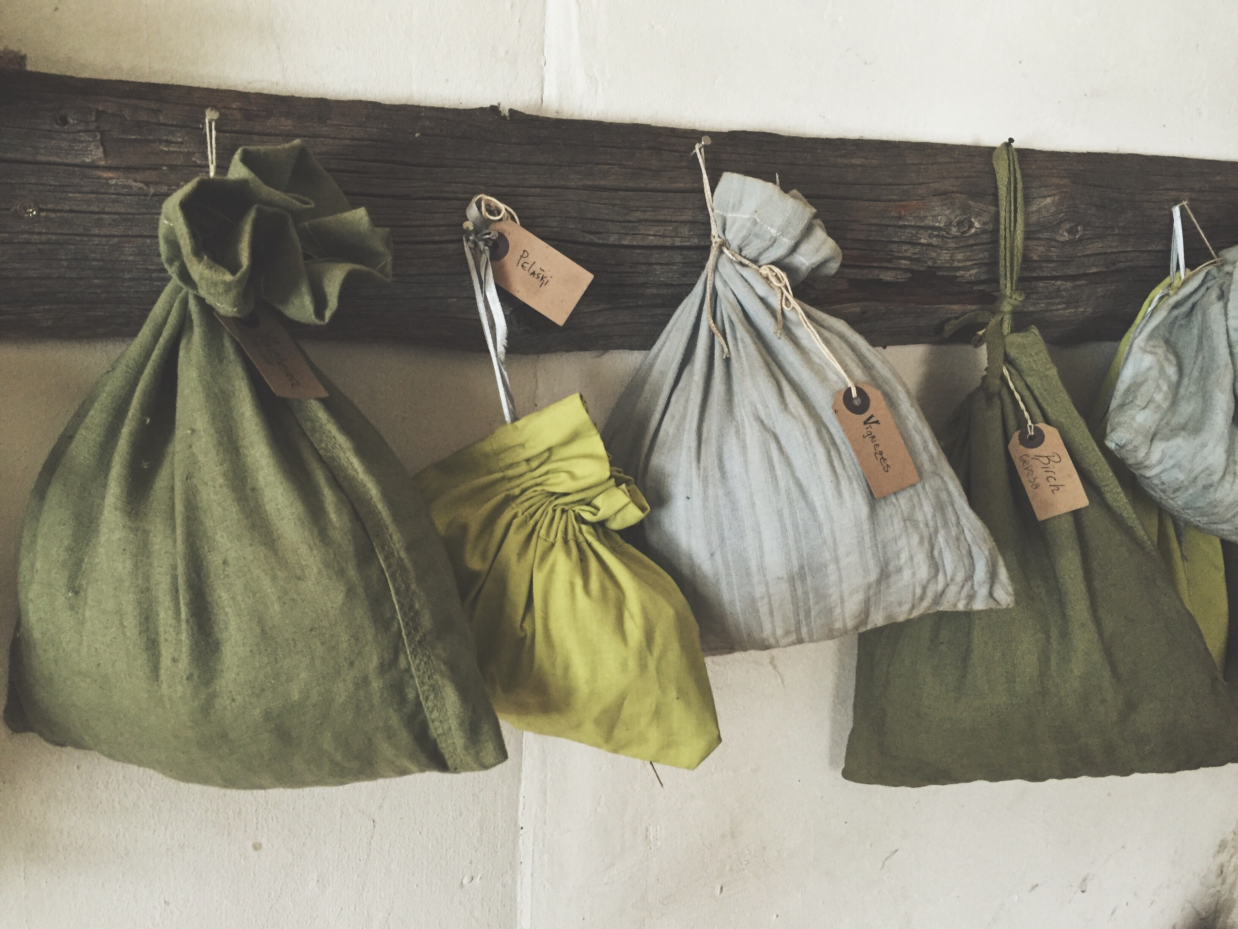 Canvas bags hang on Velta's wall, stuffed with dried leaves, twigs, berries, anything suitable for tea. © 2016 Gail Jessen, A Series of Adventures