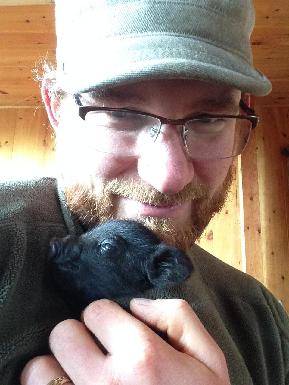 Greg cuddling a piglet