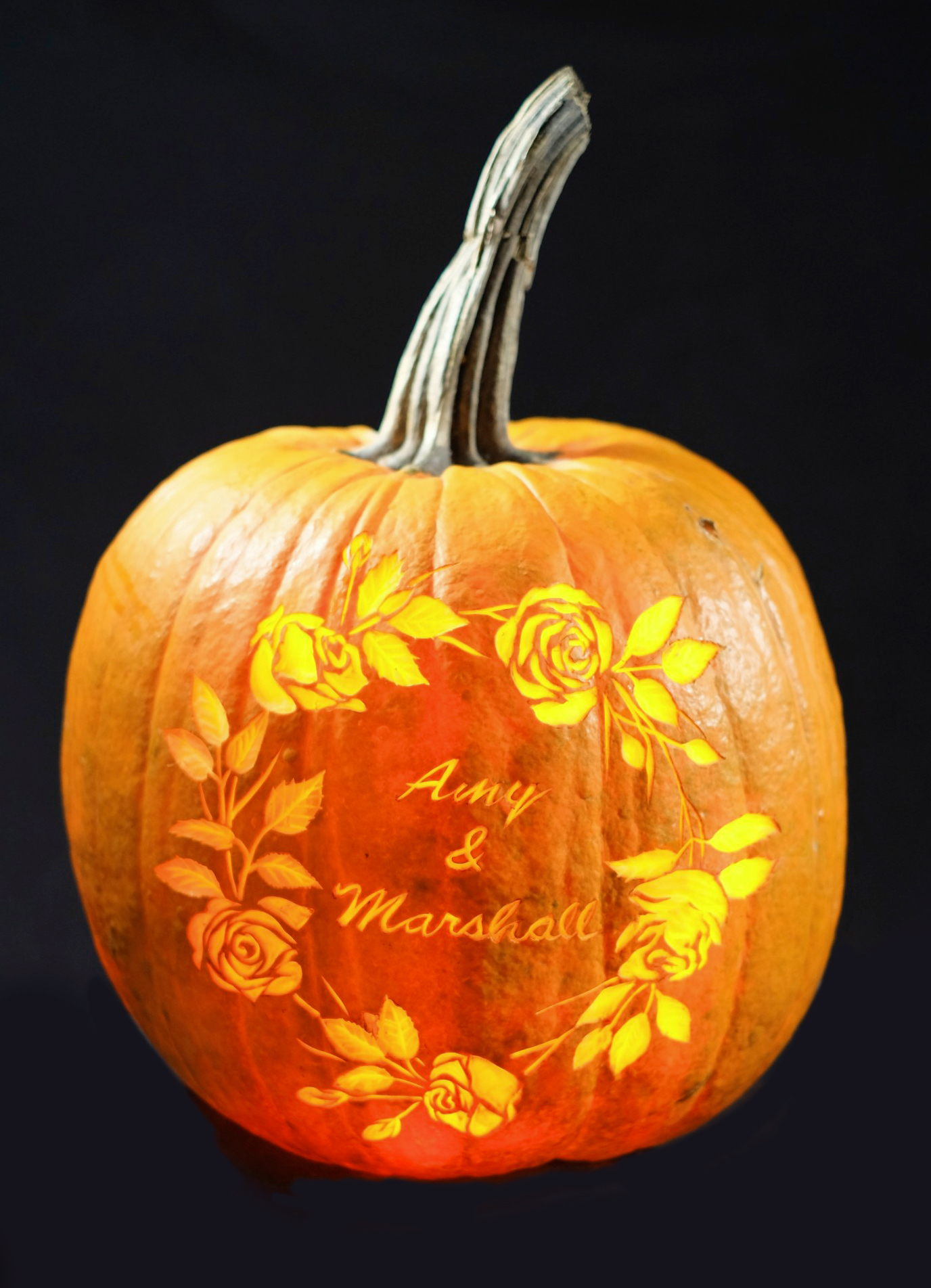 Large pumpkin with names and decorative floral art.