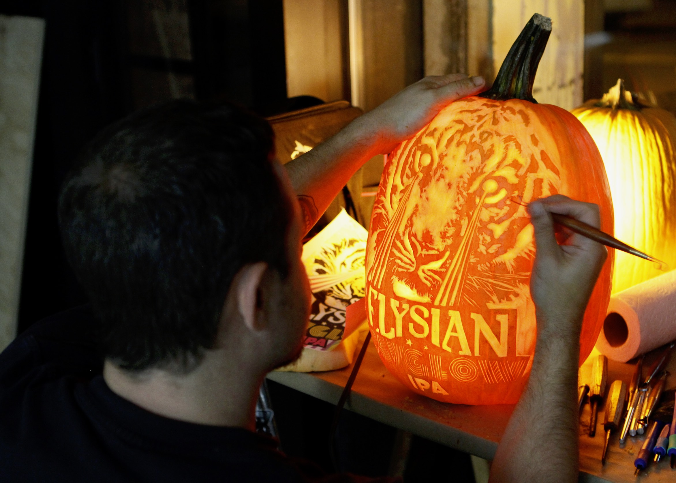 Ben carving an Xtra Large pumpkin with logo and label art for Elysian Brewing.