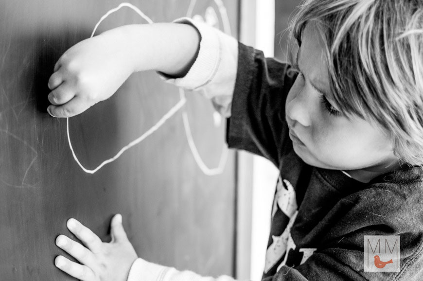 Child drawing on blackboard at day care in Chicago, IL