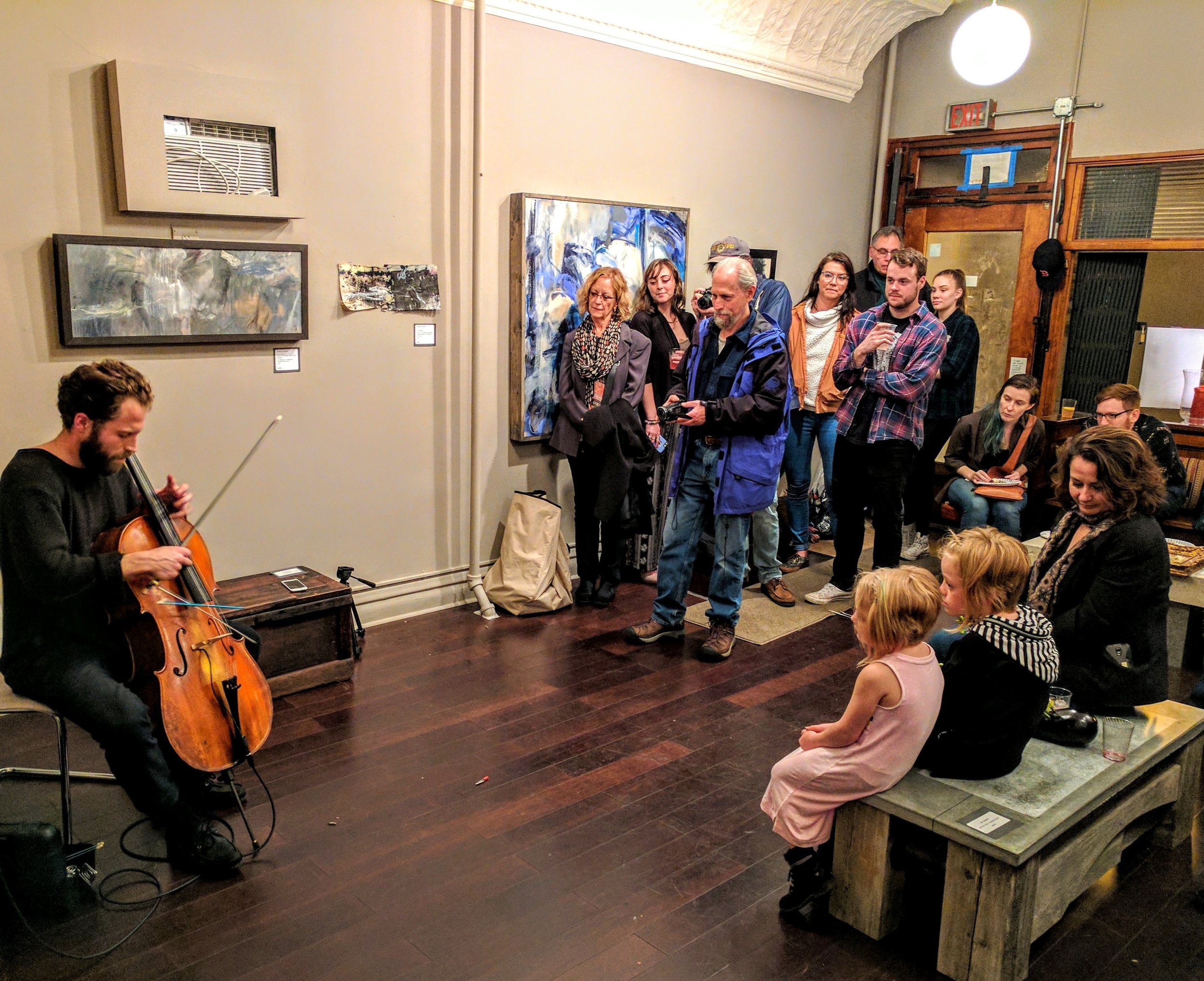 Teddy Rankin-Parker playing cello for a packed gallery during the Abstract Workshorses show.