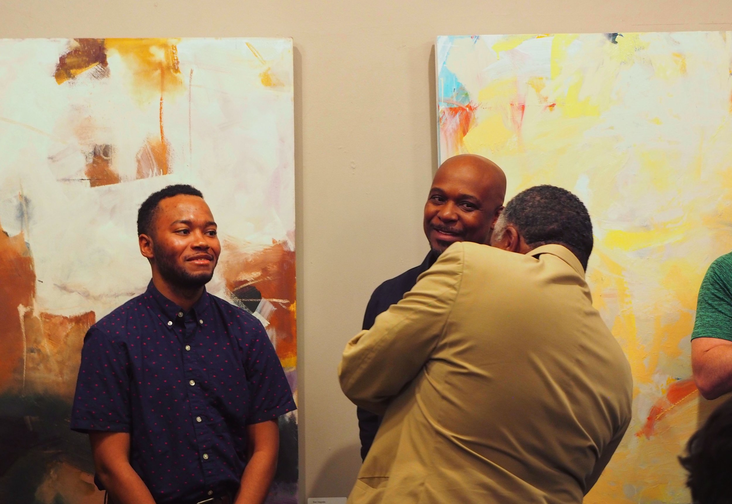 Attendees enjoying the Opening Reception. Paintings in photo by Julie Tierney and Ken Hogrefe.