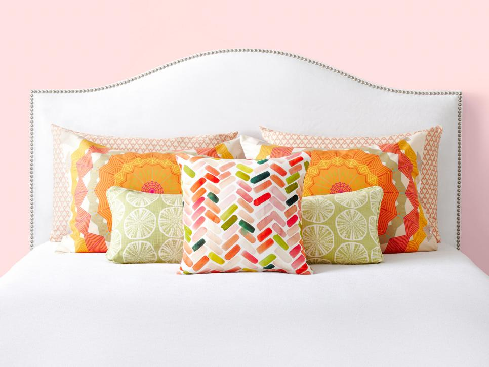 warm coloured pillows on a white bed.jpeg