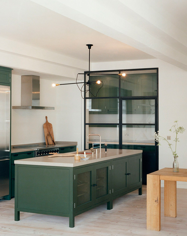 12-green-kitchens-long-island-with-dark-green-cabinets-and-cutting-boards-against-wall.jpg