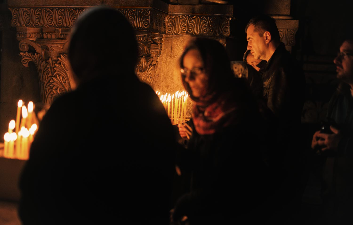 People lighting candles at the Church of the Holy Sepulcher.