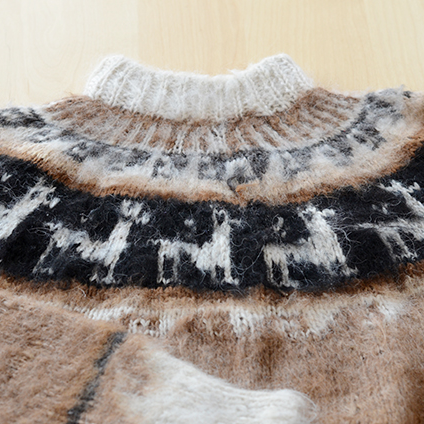 For this hand-knit Peruvian sweater, we re-used the existing yarn and reconstructed the edging on the collar to fit the owner better.