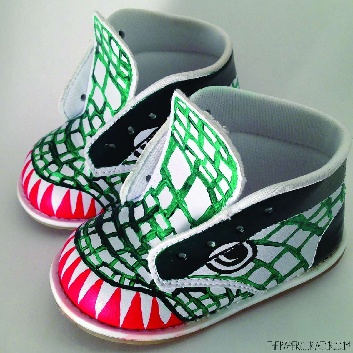 DINOSAUR SHOE WITH TEETH AND DARK GREEN COMPLETED, EYES OUTLINED AND SCALE OUTLINES STARTED.