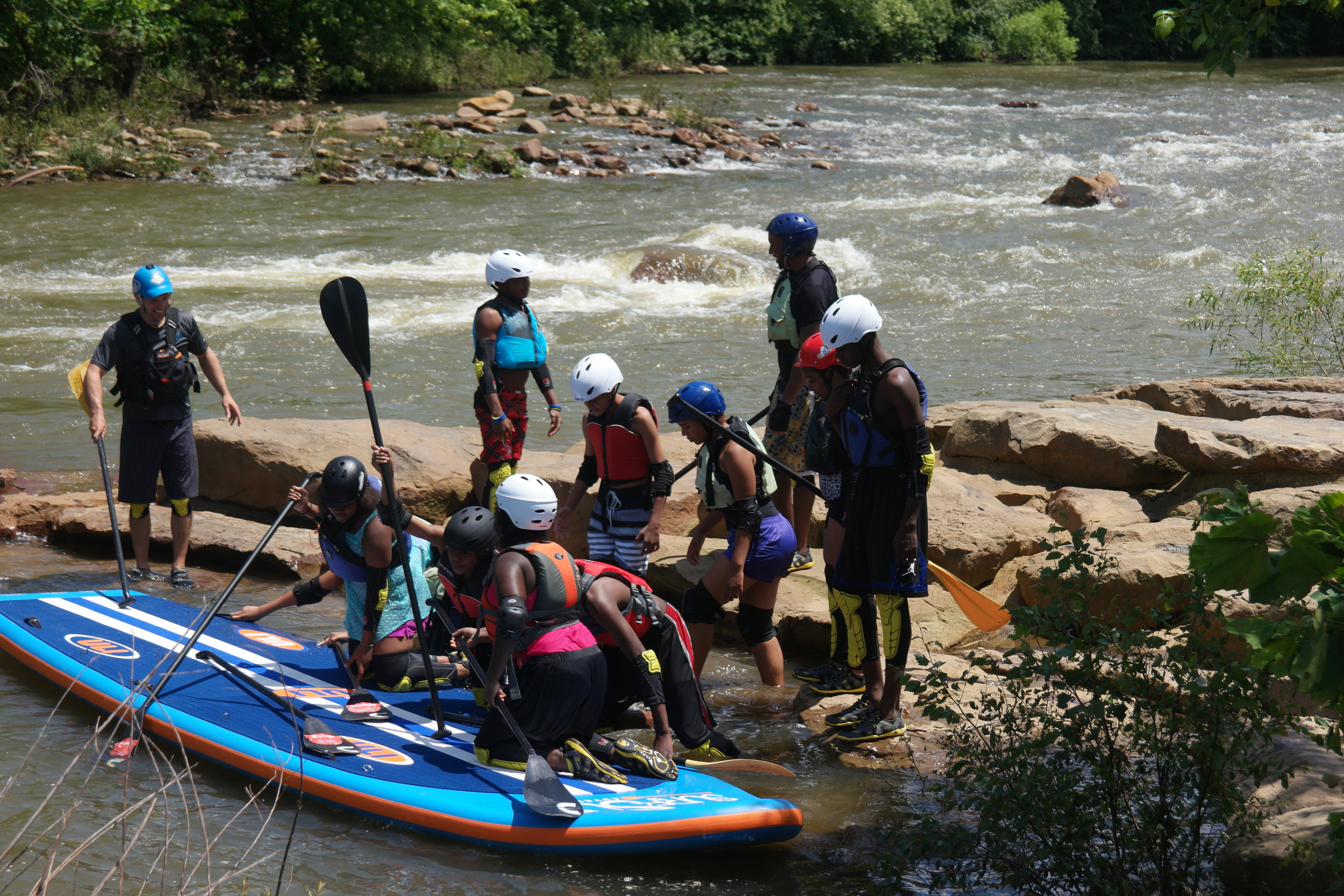 The team prepares to board the SSS SUPSQUATCH, an 18 - foot team paddleboard that they would paddle through the rapids of the Stonycreek River!