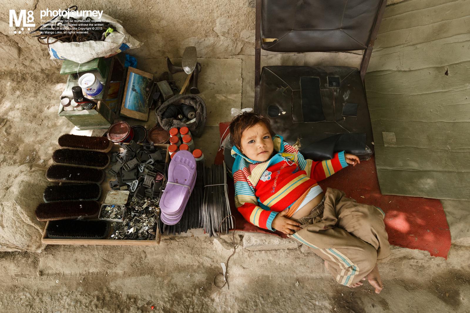 补鞋档的小孩. The Children at the Cobbler Store   India 2013CANON 1DX16-35mm F2.8L 1/80 F6.3ISO800   在Leh停留了十天,住在Changspa Road里面. 每日出门都必须经过Changspa Road大街路口. 路口旁有一印度人的补鞋档口,档口旁边还有一对年轻母子, 除了晚上,大致上每次出入路口都会看见他们, 有时候会摆起民族首饰摆卖,有时候只是坐着伸手讨吃。而那大概四五岁的小孩,有时候哭着让妈妈给喂饭,有时候嘻哈哈的与路人逗玩,这边跳跳,那边跑跑, 很自由似的自得其乐.  回顾当日一次路过拍下哪小孩的照片, 很自然的就会将他与自家国内的小孩做比较. 哪一方会哪一方比较开心?快乐?有前景?多想了,我不懂.