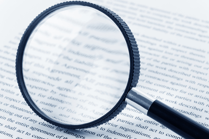 Black-magnifying-glass-over-page-of-book.jpg