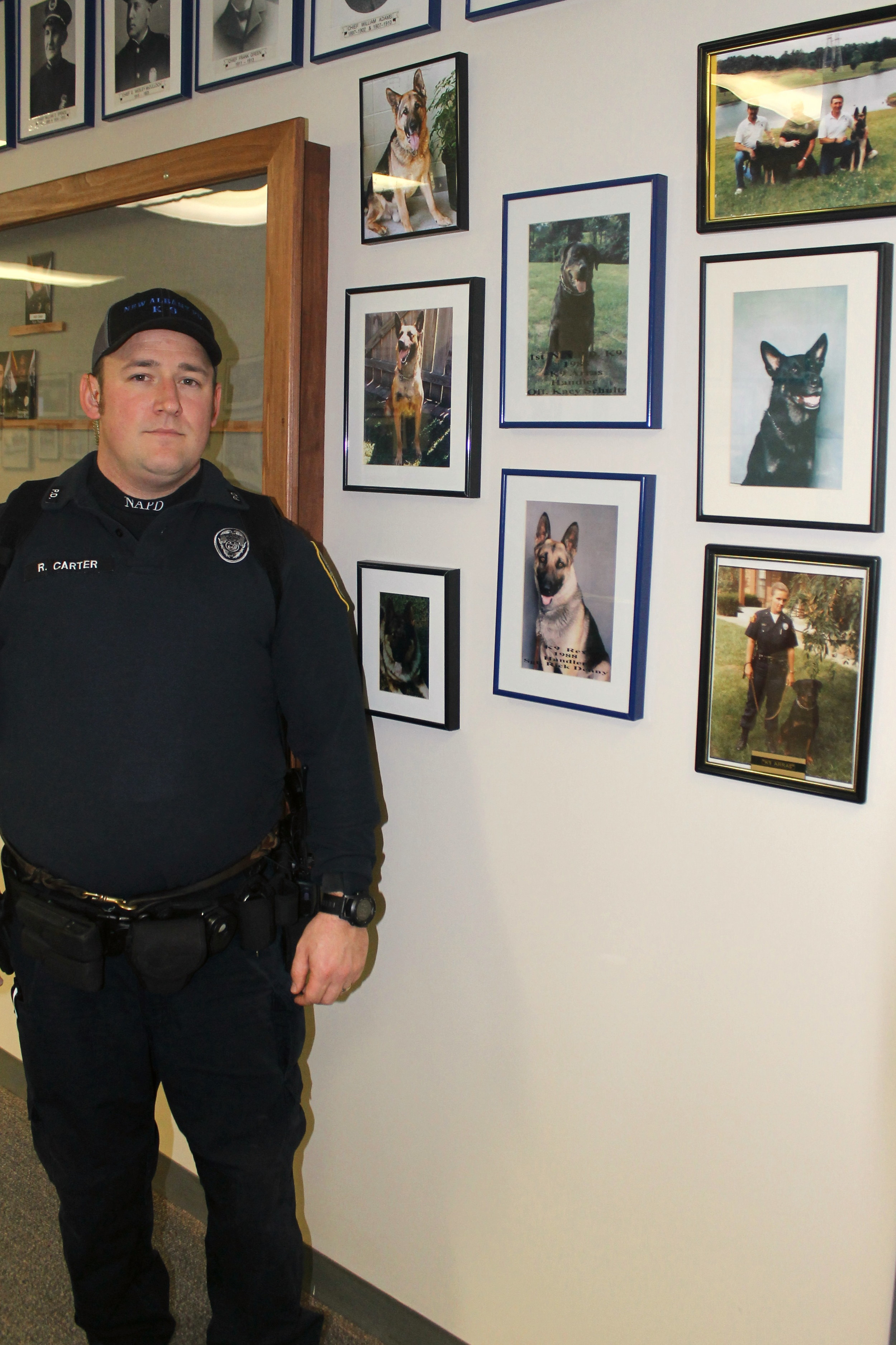 Patrolman Robert Carter, Warro's handler, is pictured with the former K-9s of the NAPD.
