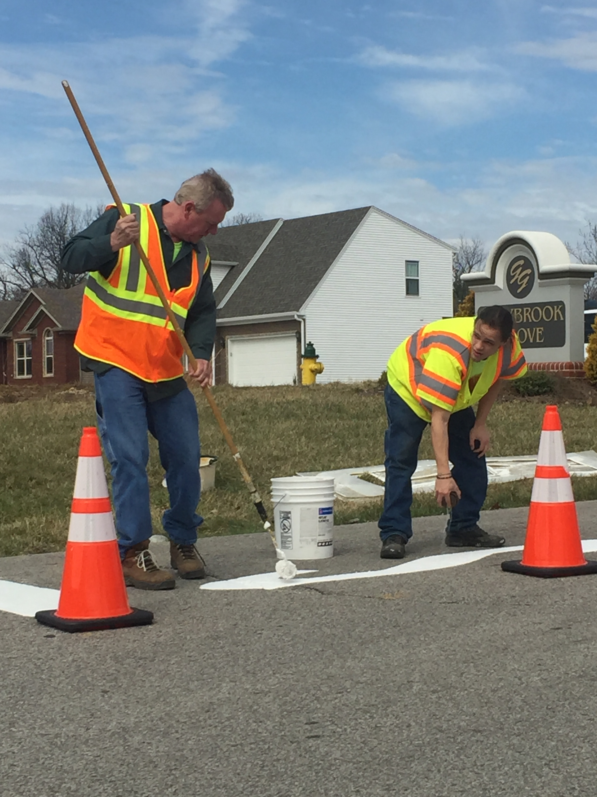 Crews work to repaint traffic signage.