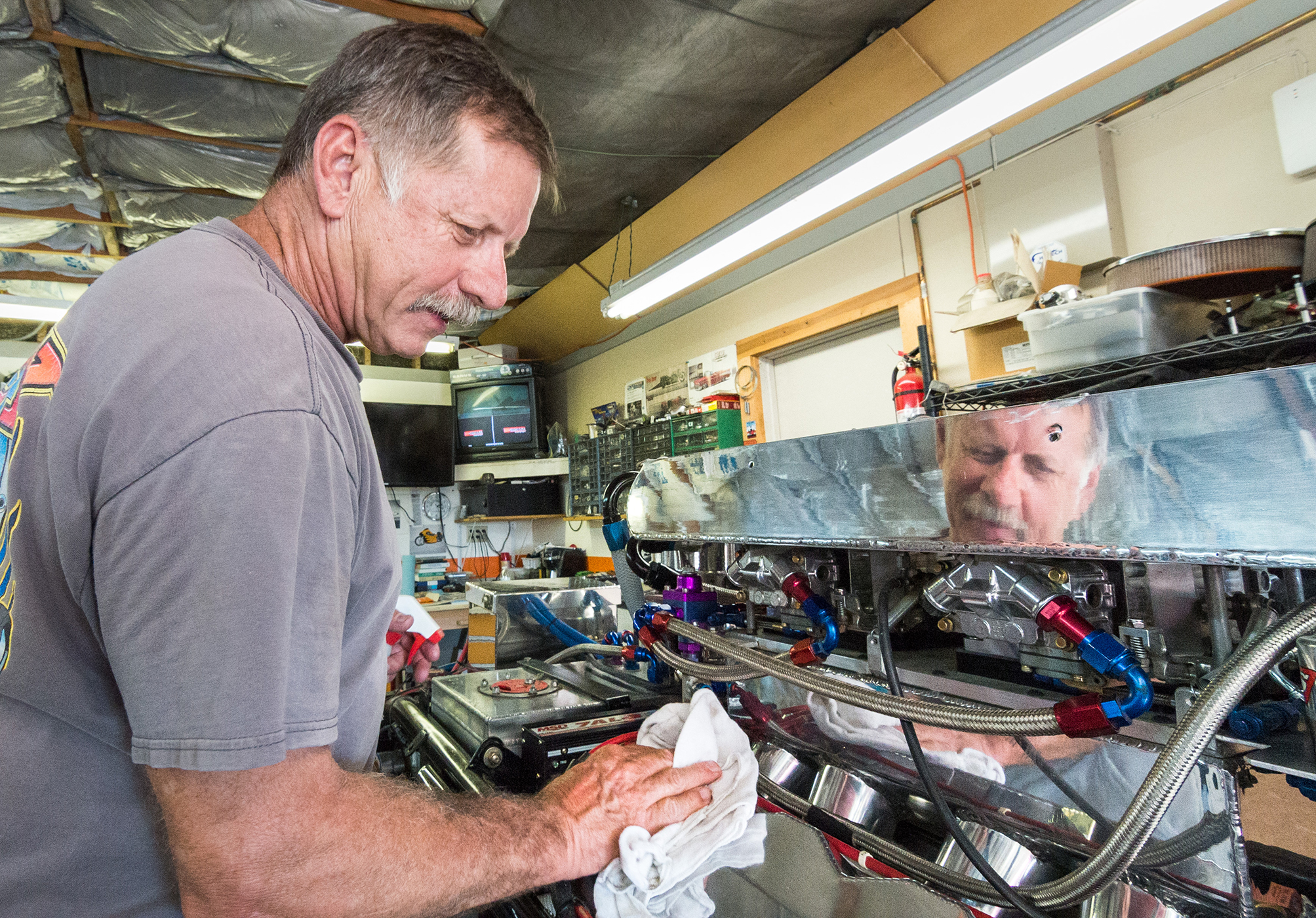 """""""One thing about this is you're always cleaning,"""" Dave Isley says while cleaning the engine bay. He jokes that it is a good thing he does not mind because half of racing is cleaning the car."""