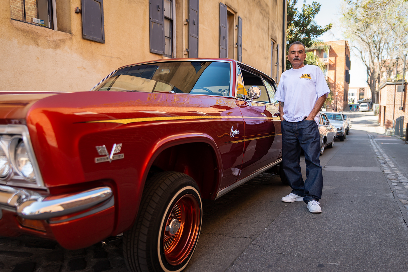 """Jackie Hader and his 1966 Chevrolet Caprice take a break in Old Sacramento after a cruise around downtown. His grandson and a few other children run to the restroom before jumping back in to the cars for another drive. Hader's lowrider is modified with hydraulics. He controls the height of each wheel with switches near the driver's seat and can make the front bounce off the ground. This is called """"hopping."""""""