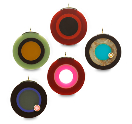 Pendants made from vintage bakelite pieces mounted in 18 karat gold and set with colored sapphires.