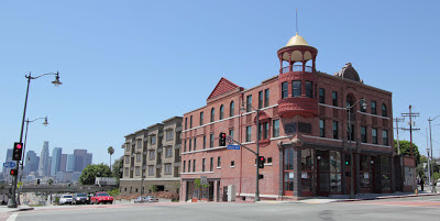 The oldest remaining commercial building in Boyle Heights is set prominently at the intersection of First and Boyle, outlined against a backdrop of downtown Los Angeles skyscrapers