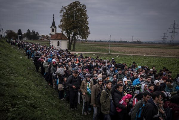 Migrants walk past the temple as they are escorted by Slovenian riot police to the registration camp outside Dobova, Slovenia, Thursday October, 22, 2015, Sergey Ponomarev
