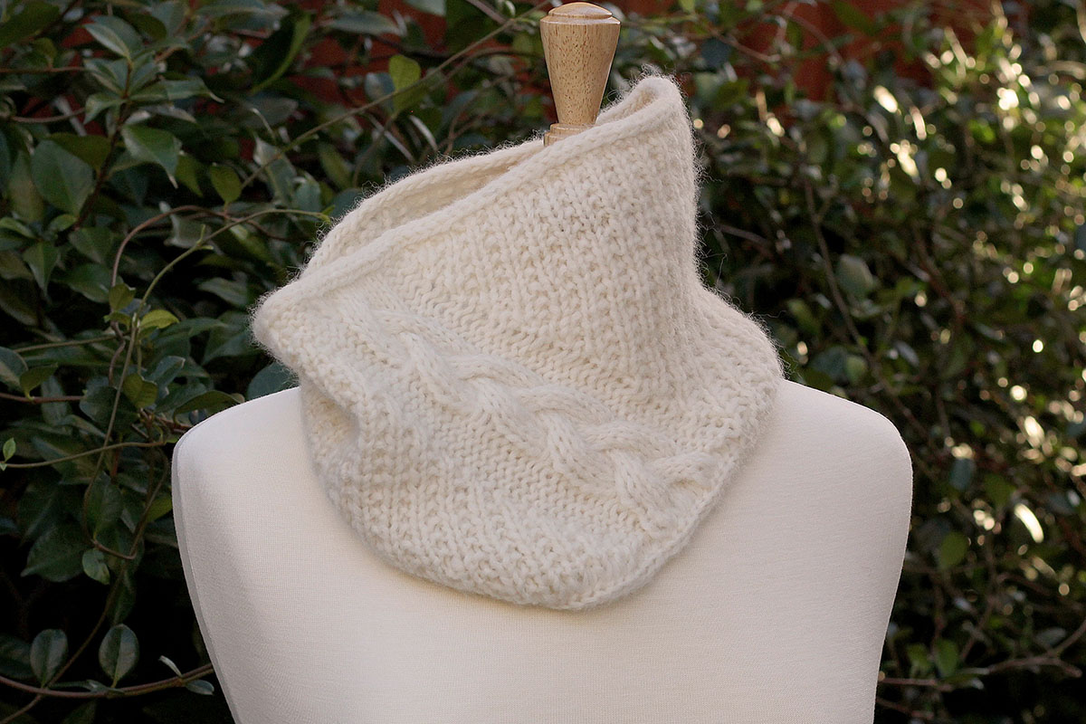 A garter-rib cowl, knit in the round, with a wandering braid cable.