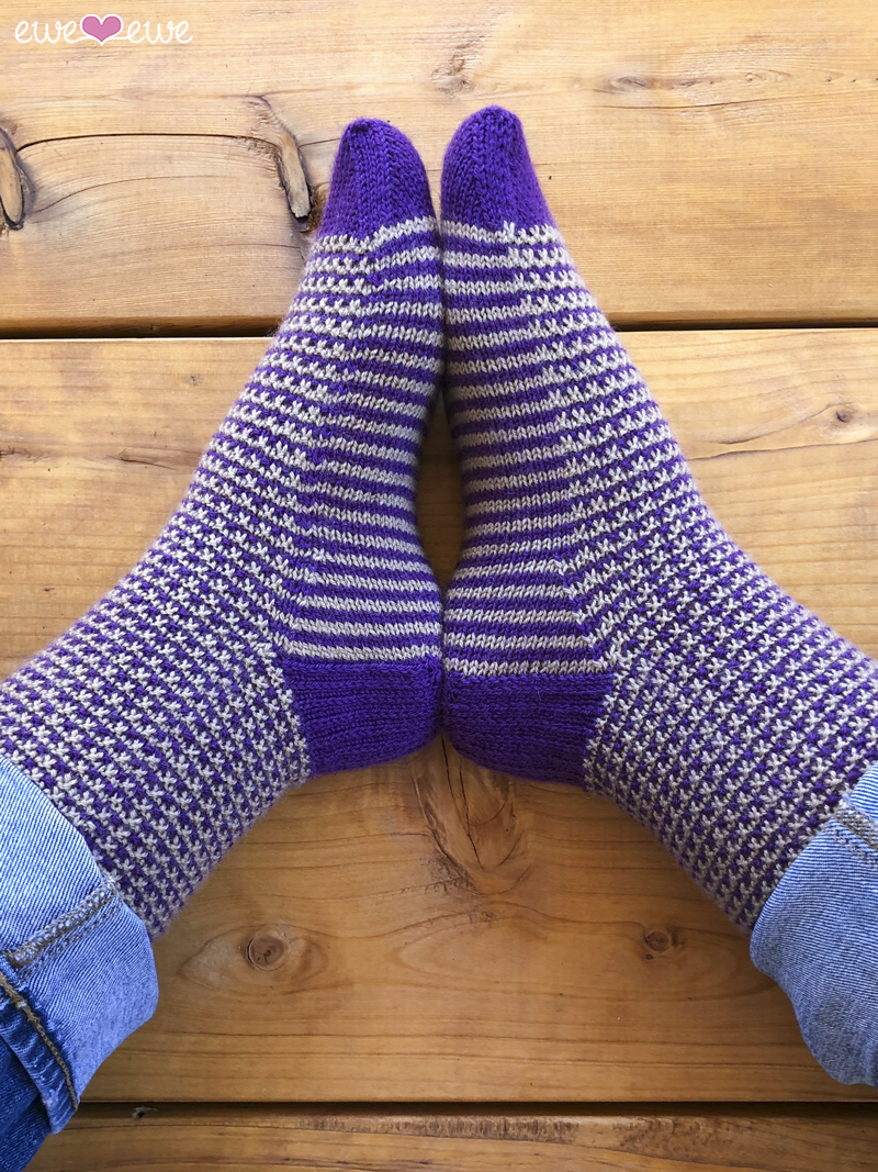 Stripe It To Me  (Ewe Ewe Yarns, featuring Fluffy Fingering): These adorable cuff-down socks highlight the contrast between a neutral and a pop of color! Suitable for men and women, these addictive-to-knit socks are a visual treat: depending on which way you look at them, the stripes run vertically  OR  horizontally!