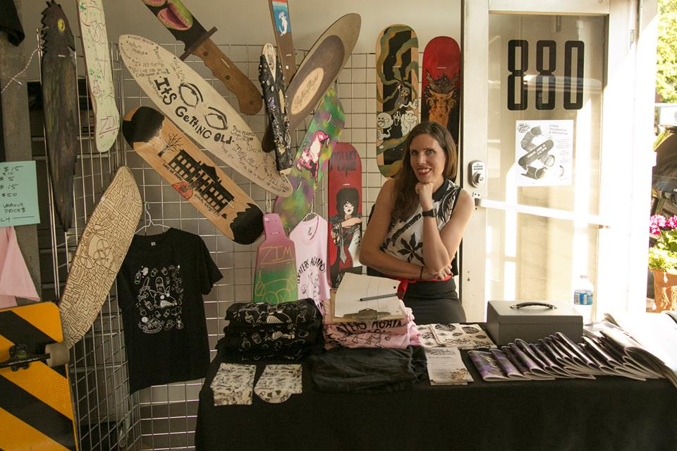 Oasis teacher Lauren holding down the merchandise table with tons of student-made boards, clothing and zines that support the ongoing program.