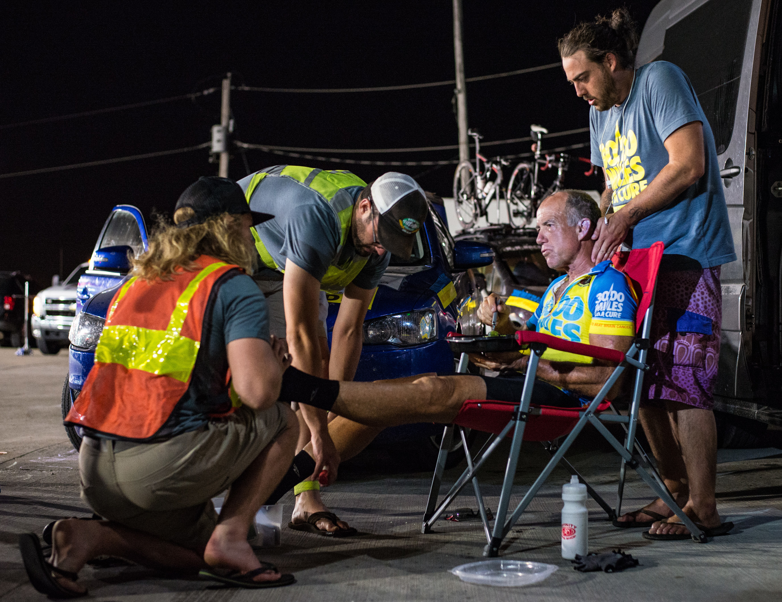 From left to right, crew members Ryan Jean, Tyler Jandreau, and Jesse Reeves massage Marshall as he eats to get him ready for a full night of riding. Marshall had little time to stop as he was trying to make it to the Mississippi River time cutoff. Photo taken on June 22nd, 2016.