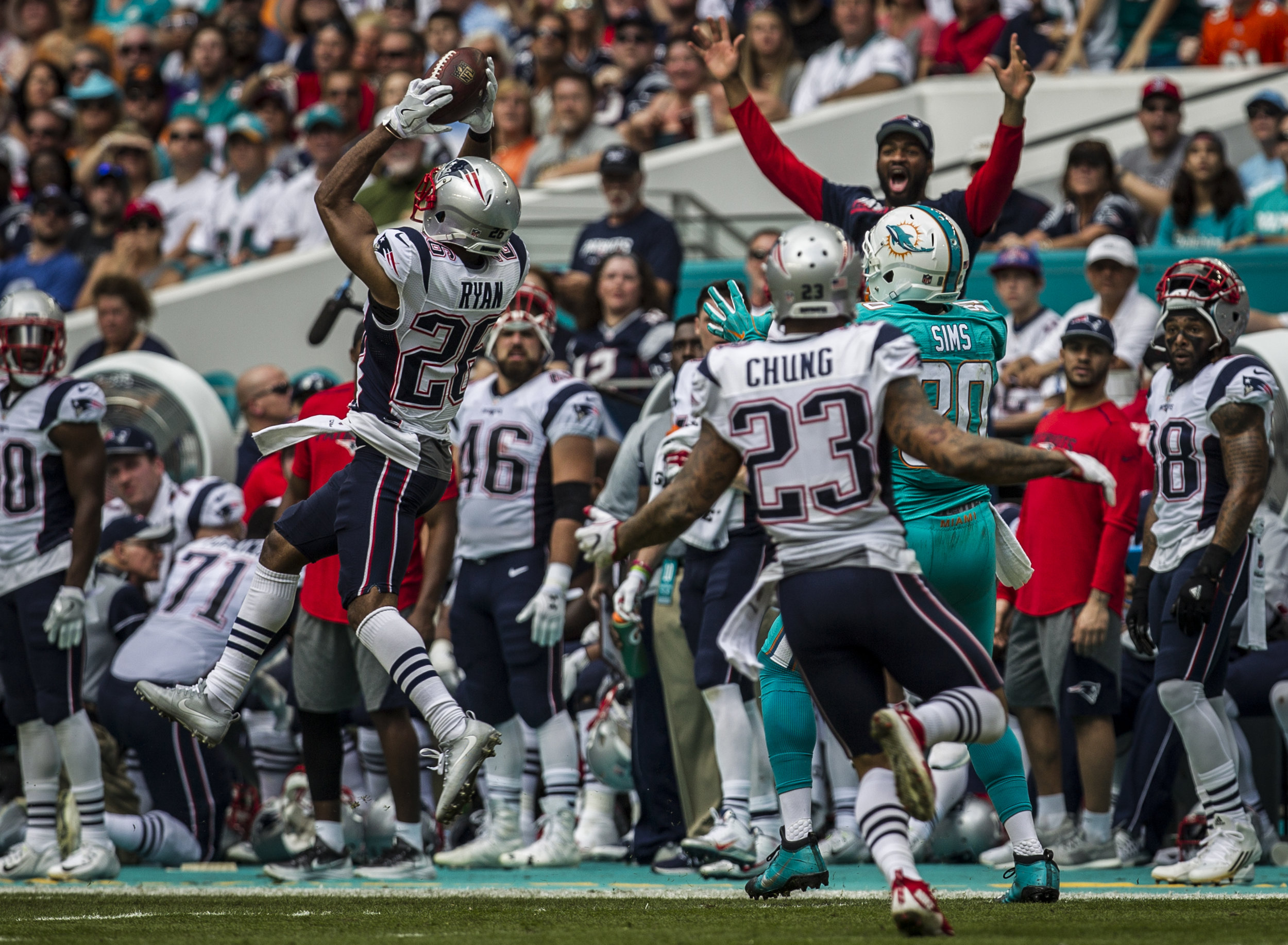 New England Patriots cornerback Logan Ryan (26) intercepts a pass intended for Miami Dolphins tight end Dion Sims (80) as the Patriots sideline celebrates at Hard Rock Stadium in Miami Gardens, Florida, January 1, 2017.