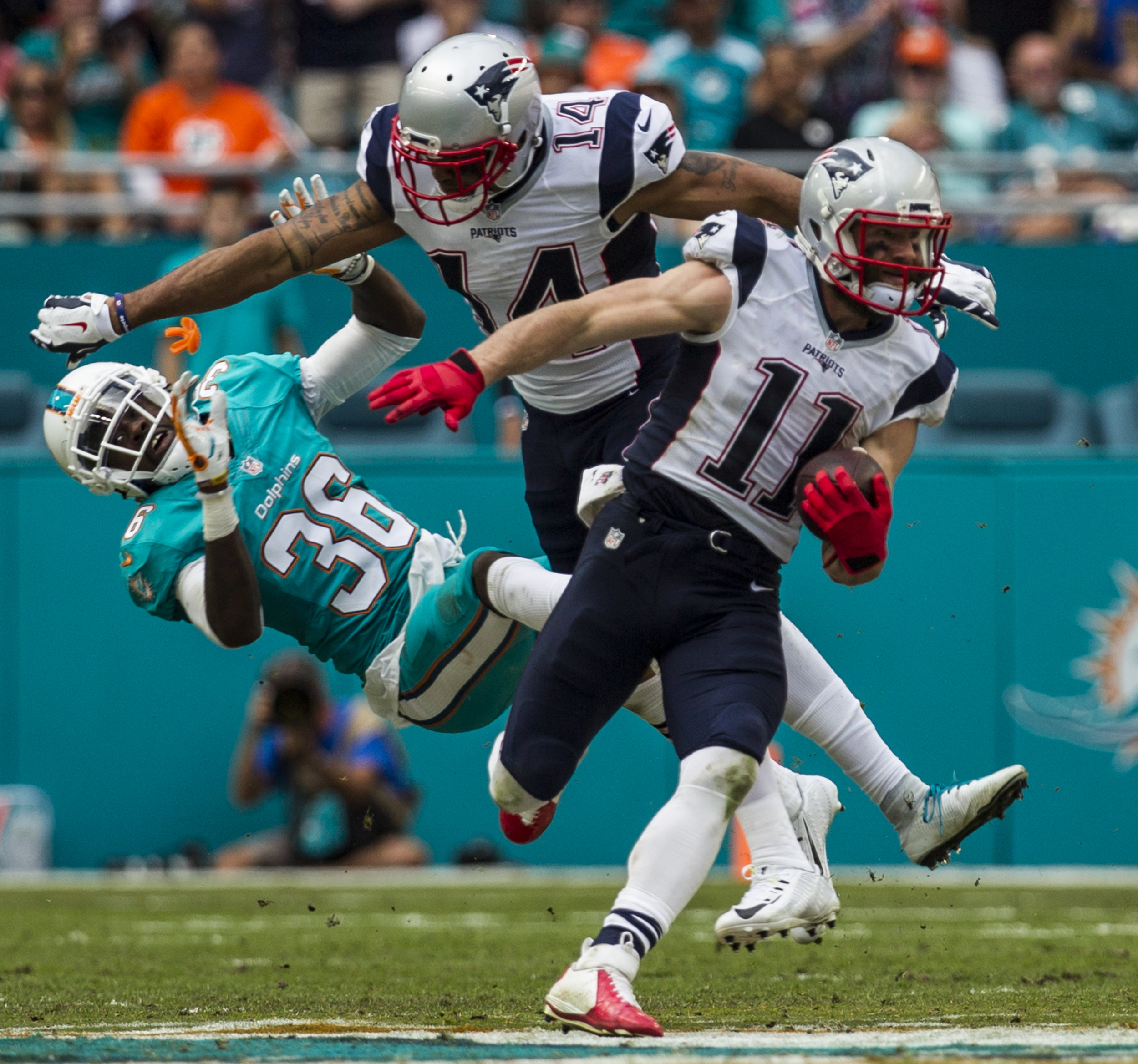 Miami Dolphins cornerback Tony Lippett (36) gets blocked by Patriots receiver Michael Floyd (14) as Julian Edelman (11) breaks free for a touchdown at Hard Rock Stadium in Miami Gardens, Florida, January 1, 2017.