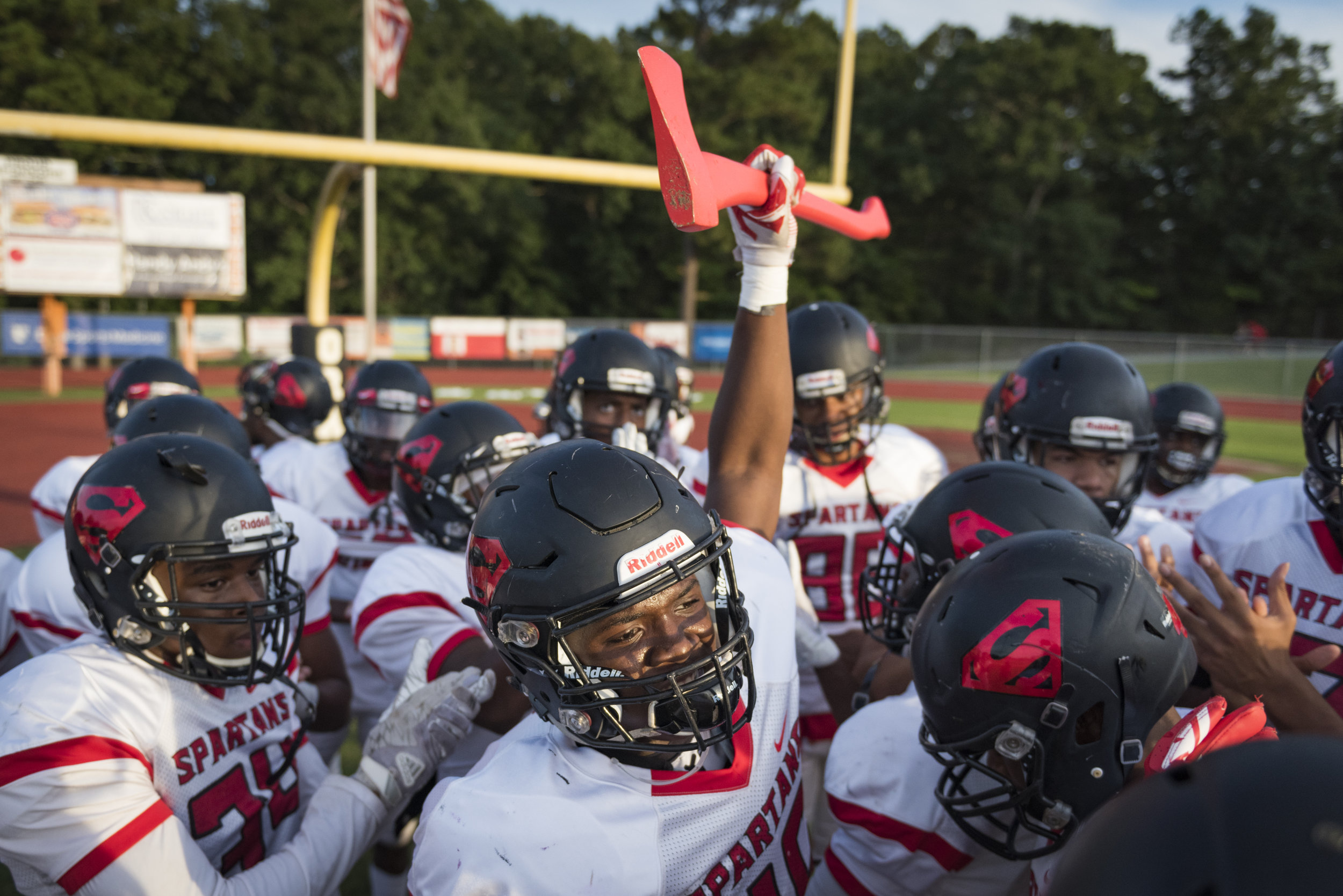 Southern Durham junior linebacker Jaki Brevard raises the team axe before the Spartan's game against Orange Highschool in Hillsborough, North Carolina. The team captain usually carries the axe before games.