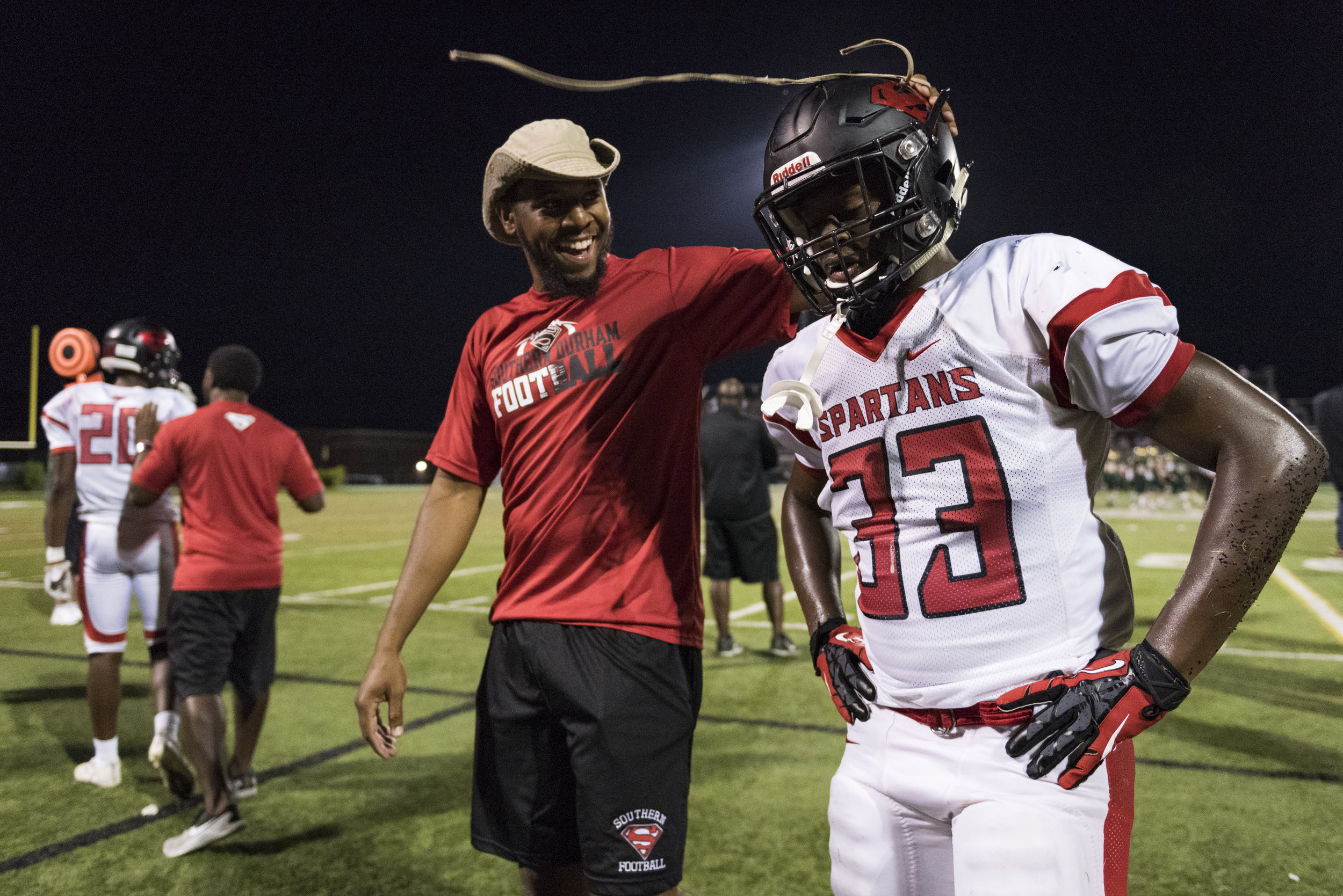 Southern Durham assistant coach Chris Smith celebrates with linebacker Jakhari Dowd (33) after a big play against Cardinal Gibbons High School. The Spartans had 18 coaches on staff this year, mostly comprised of past players that want to give back to their high school team.