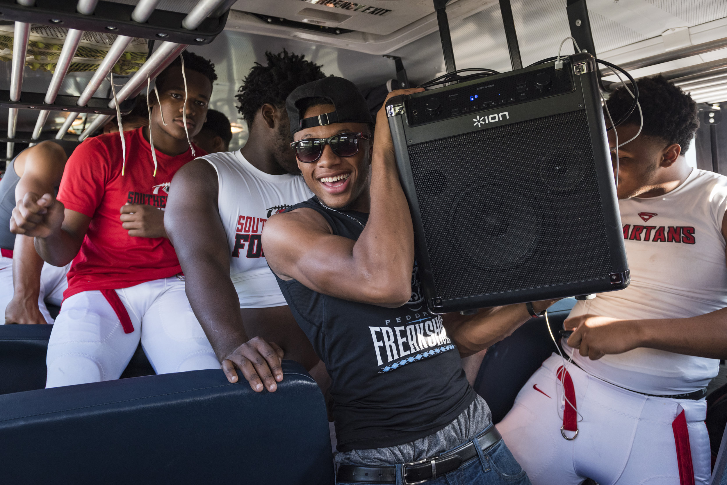 Southern Durham junior wide receiver Devin Smith carries the team speaker inside of the bus. Smith, one of the team's best players, was not playing due to injury but that did not stop him from starting the party before the game.