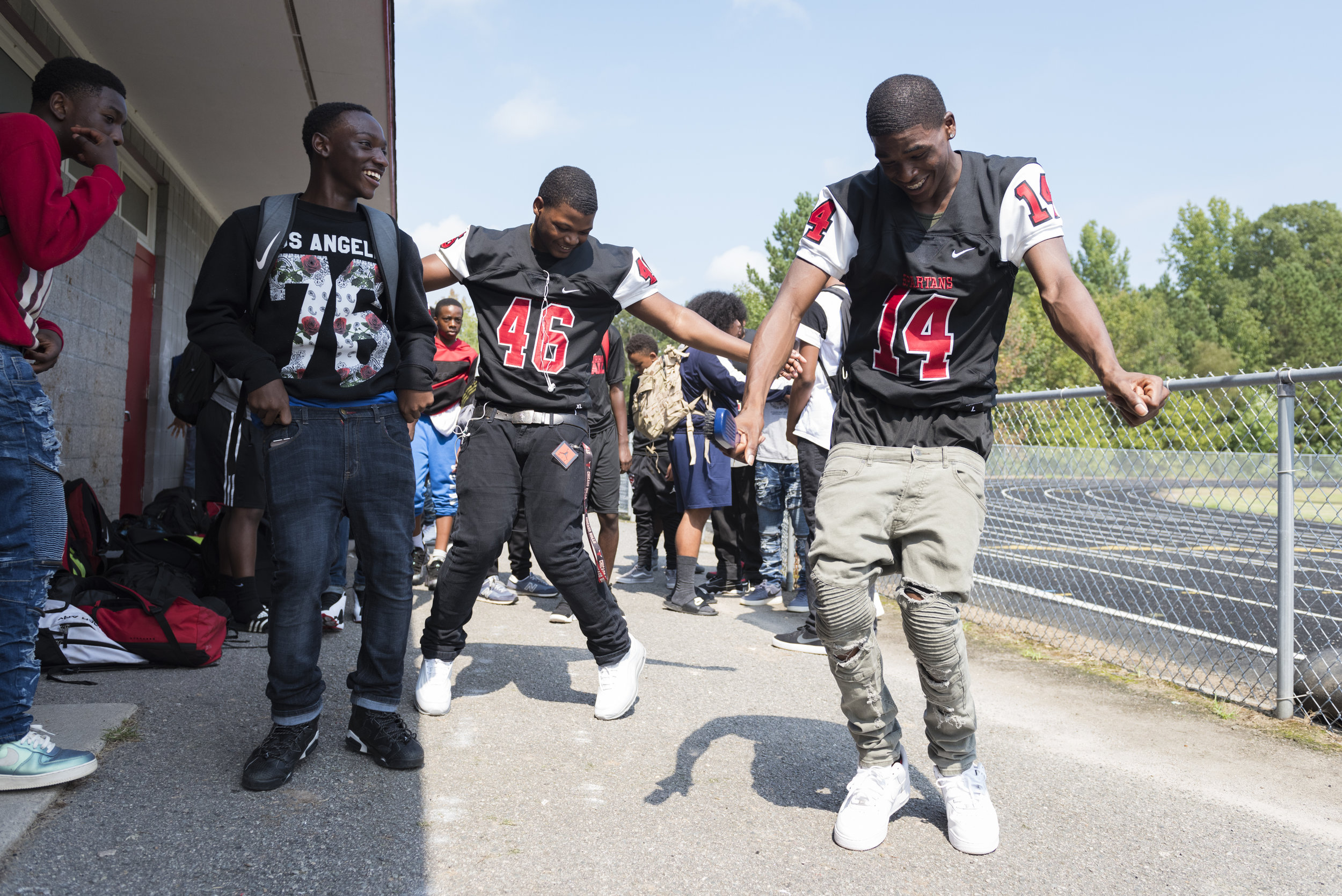 Southern Durham players Lavar Houze (46) and Cinsere Clark (14) dance during the team's homecoming pep-rally at school.