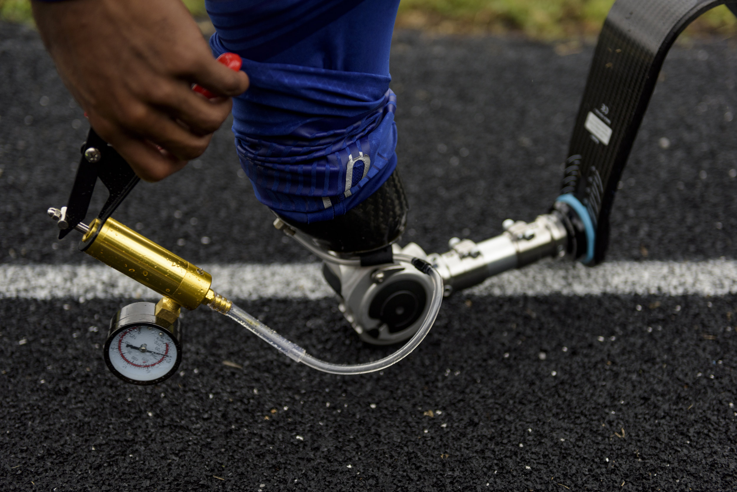 U.S. Paralympian Desmond Jackson regulates the pressure in his prosthetic leg before a race in Durham, NC on June 8, 2019.
