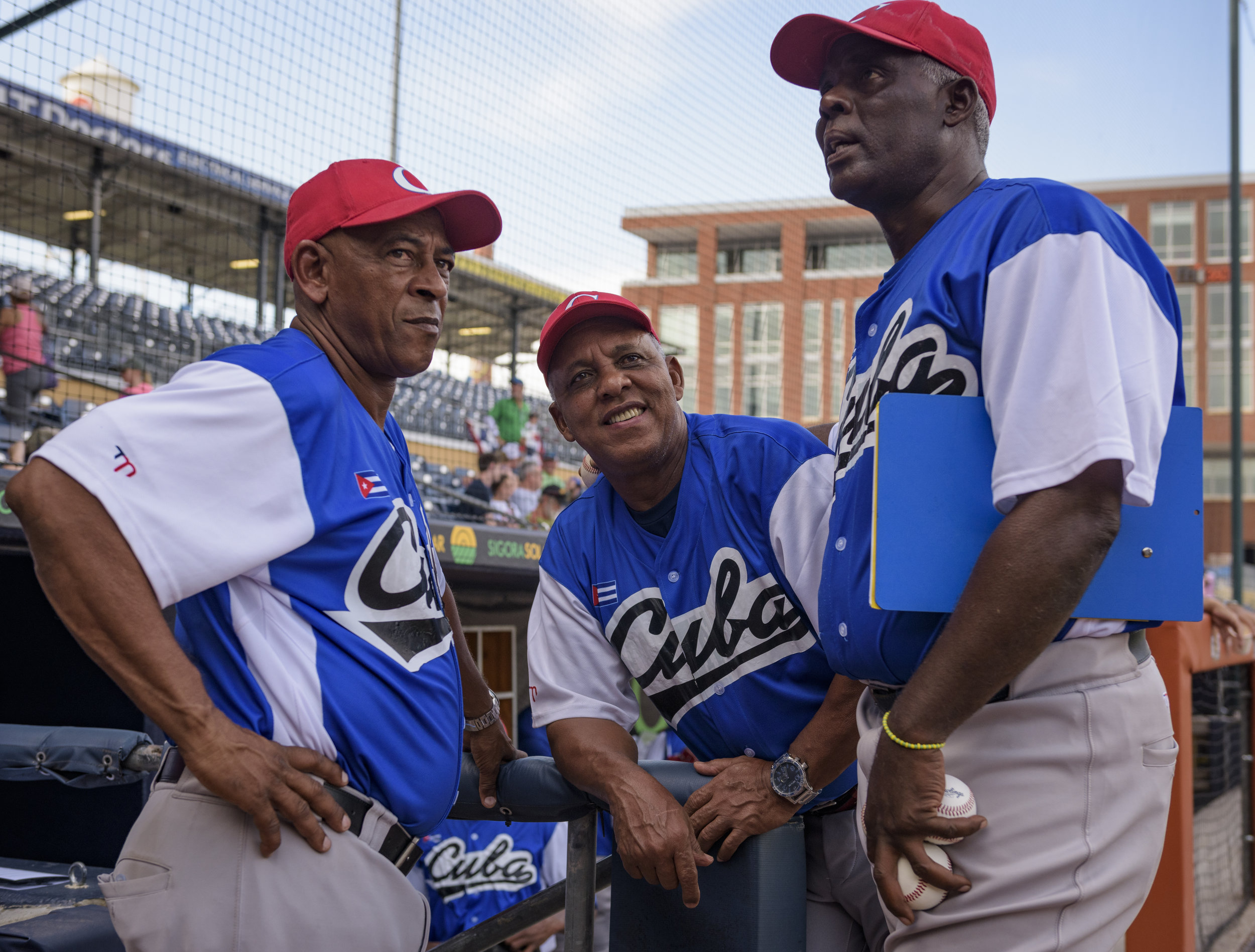 Cuba national team manager Rey Anglada (center) talks with coaches Miguel Rojas Rodriguez (left) and Javier Galvez Cordova (right) before Cuba's game against the USA Baseball Collegiate National Team on July 6, 2019 at Durham Bulls Athletic Park in Durham, NC.