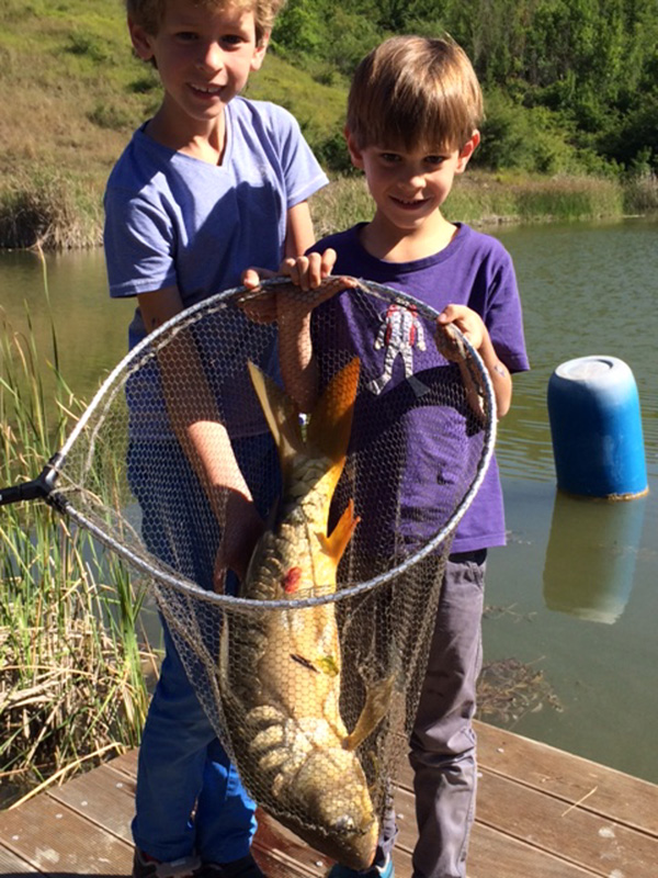 Two young guests caught a huge carp in the fishing pond in Fattoria Barbialla Nuova