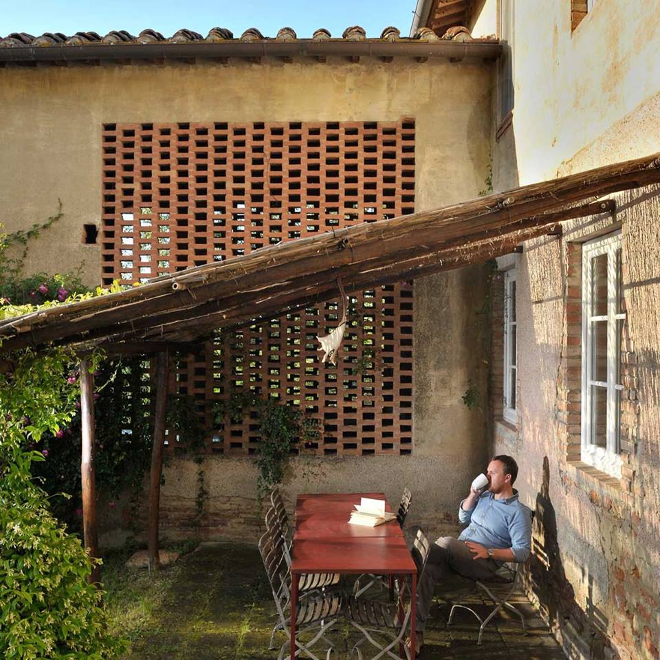Man drinking tea in the sunset under a pergola next to a rustic Tuscan house.