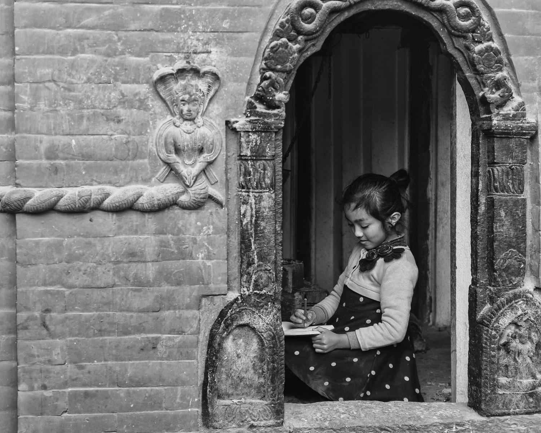 Girl doing homwork in a little temple (Kathmandu/ Nepal) - Copyright: Daniel Hofmann