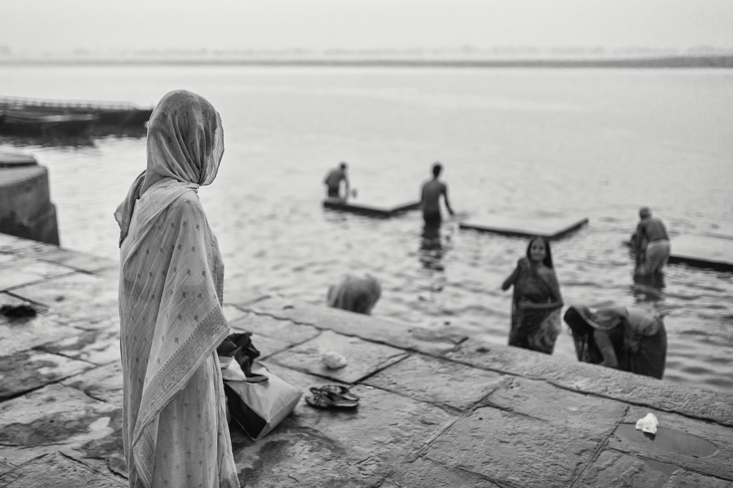 A woman is watching other people taking a bath in the Ganges. She wears a white Saree because she is widowed  –  a tradition of Hinduism. (Varanasi/ India) Copyright: Daniel Hofmann