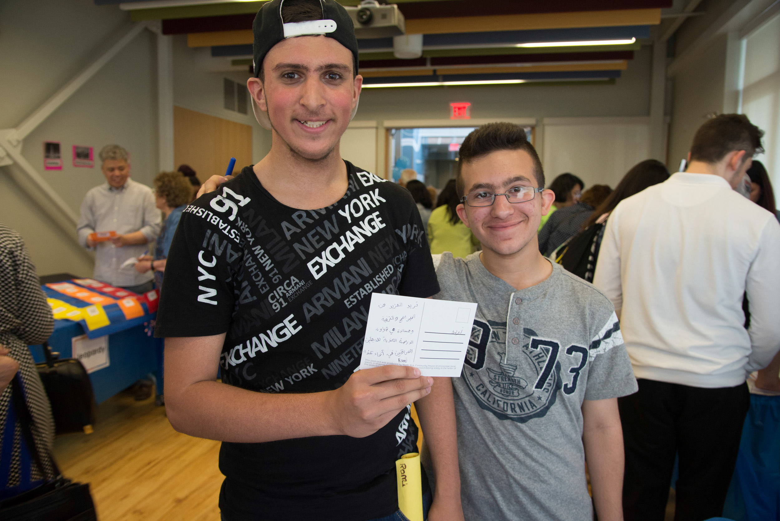 Two young participants show off a postcard to their elected official