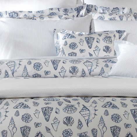 """Seashells—what Lulu DK calls """"the ocean's amazing gift""""—get pared down and abstracted in this new coastal design. Woven and printed in Italy on our Luca 500 thread count Egyptian cotton percale, Capri boasts rich indigo imagery with highlights of azure for a chic painterly effect."""