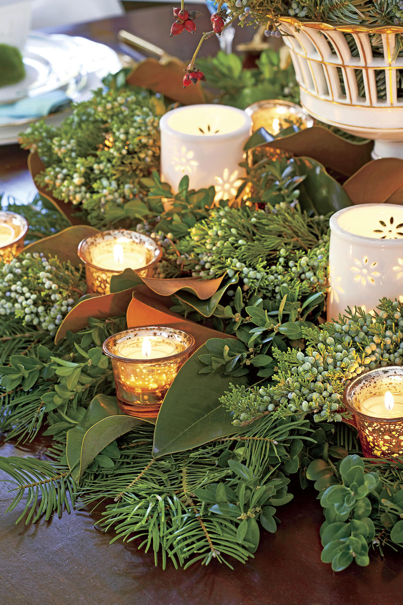 Scatter votives of different sizes throughout fresh greenery on the table for a simple centerpiece that doesn't have to be watered.