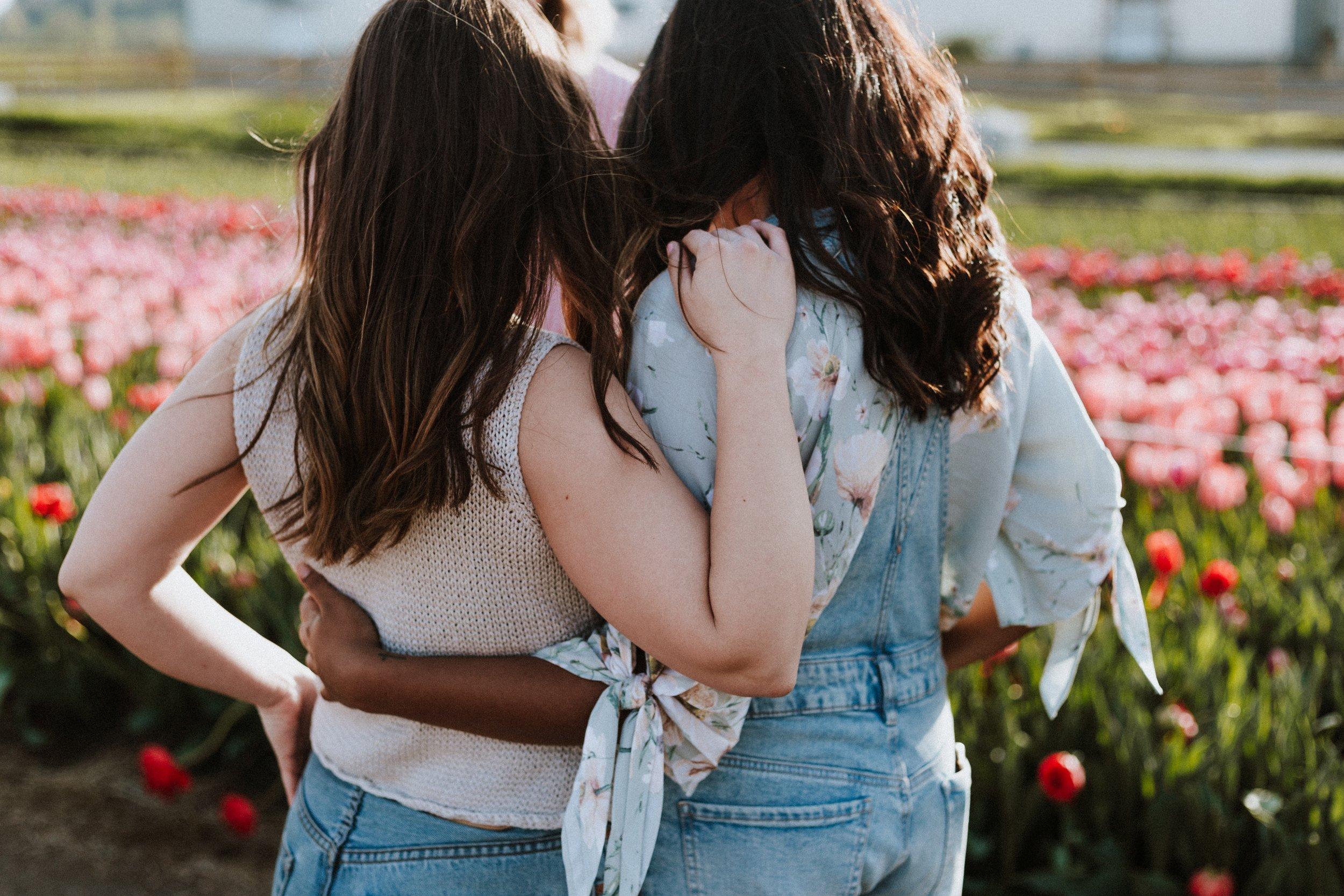 women hugging by flowers.jpg