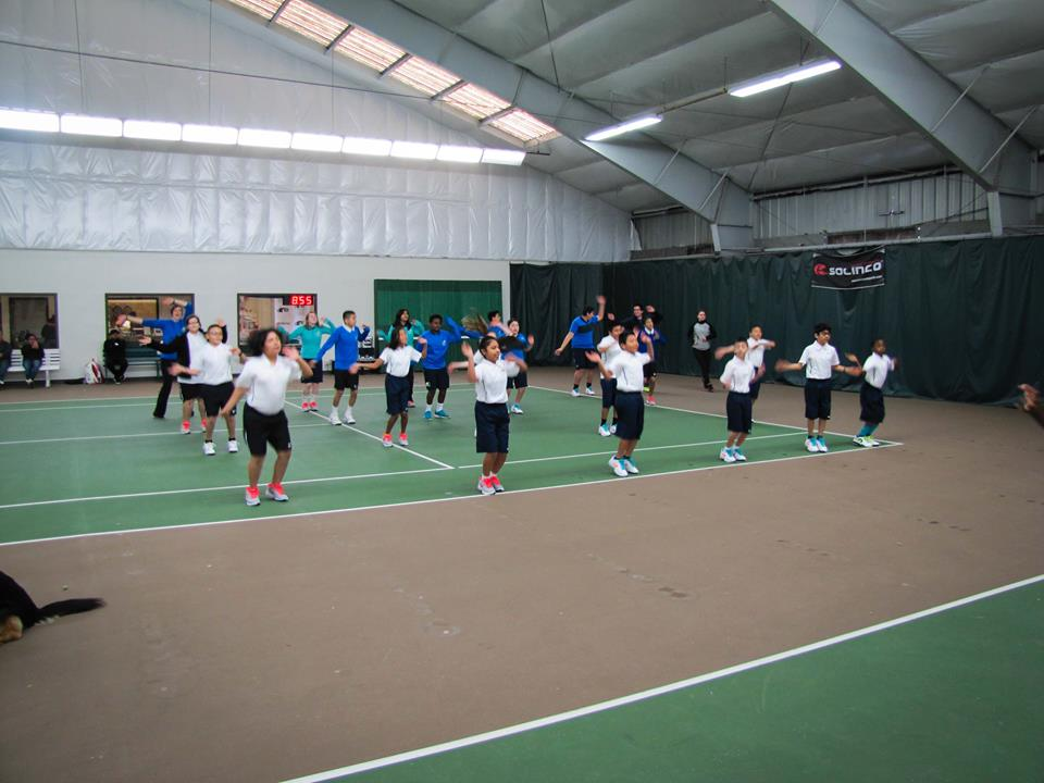 """Scholar Athletes and Coach/Tutors warm up for the junior clinic on Sunday by moving their feet and pumping their arms to """"Waka Waka."""""""