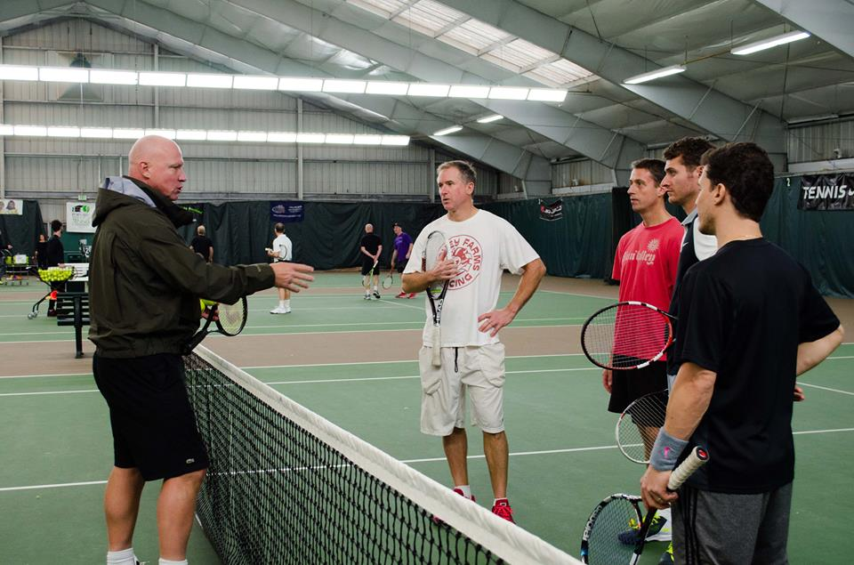 Luke Jensen gives a group of tennis players in the adult clinic instructions for the upcoming drill.